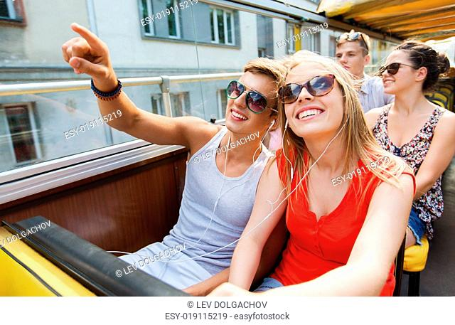 travel, tourism, summer vacation, sightseeing and people concept - happy teenage couple in sunglasses traveling by tour bus and listening to music with...