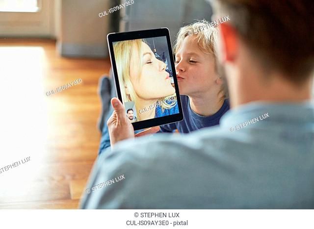 Boy kissing mother during digital tablet video call