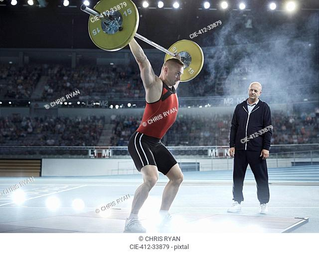 Coach watching male weightlifter squatting barbell overhead in arena