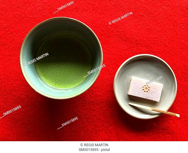 A bowl of japanese green tea and a traditional sweet cake viewed from above against a red background
