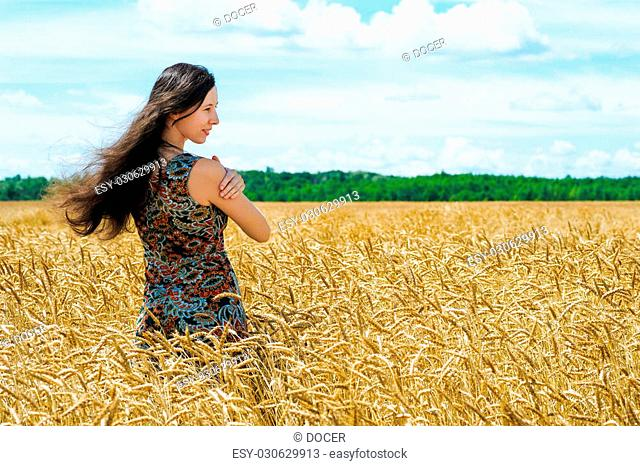 young woman standing in a wheat cereals field