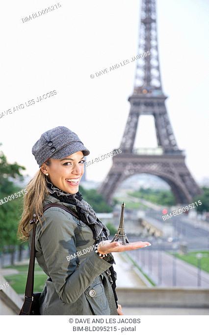 Hispanic woman holding a souvenir Eiffel Tower near the actual Eiffel Tower