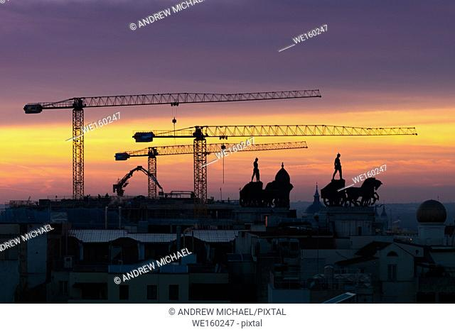 Silhouettes of Madrid skyline where cranes complement the traditional sculptures