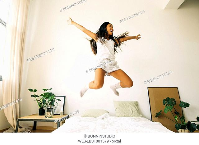 Exuberant young woman jumping on bed
