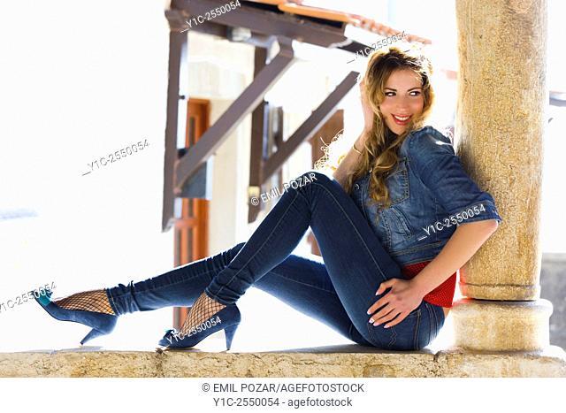 Young woman posing in denim pants
