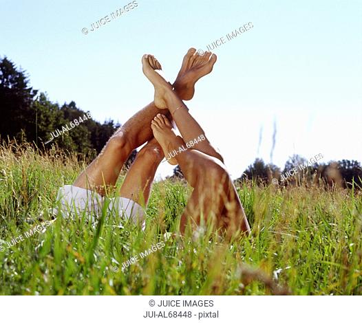 View of a man's and woman's legs sticking up out of tall grass