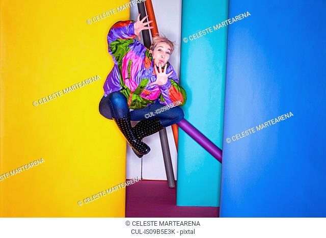Woman in photo studio, jumping, in mid air, against different coloured rolls of paper