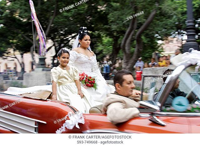 A bride and groom cruising the streets in an open convertible car