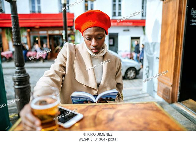 Young woman in Paris drinking beer in cafe and reading a book