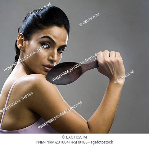 Portrait of a woman holding a wooden spoon