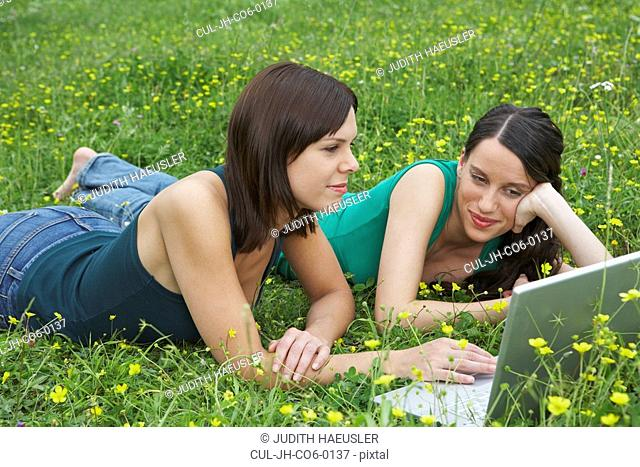 Two young women lying in meadow looking with laptop