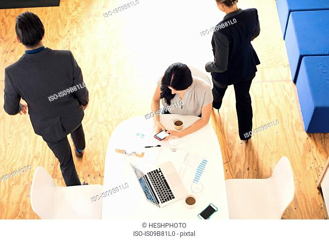 Overhead view of young businesswoman looking at smartphone at office table