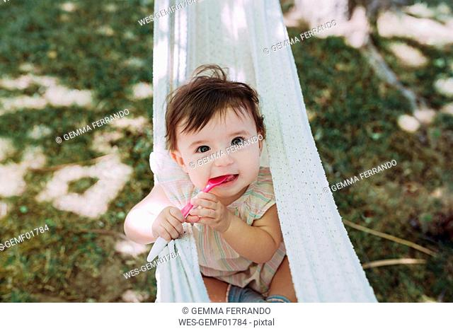 Portrait of hungry baby girl with spoon in mouth in the garden