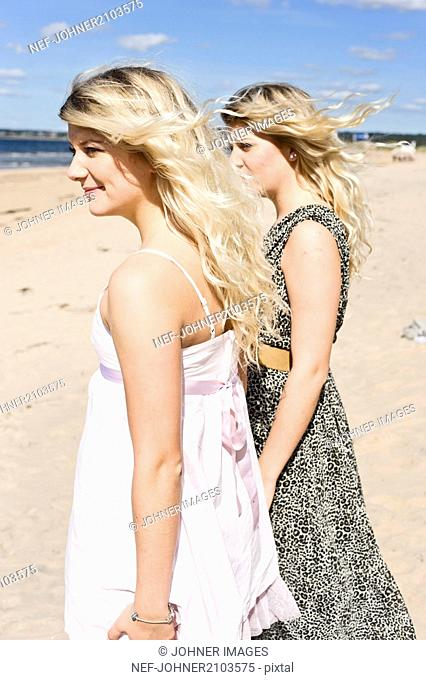 Young women standing on beach and looking at sea