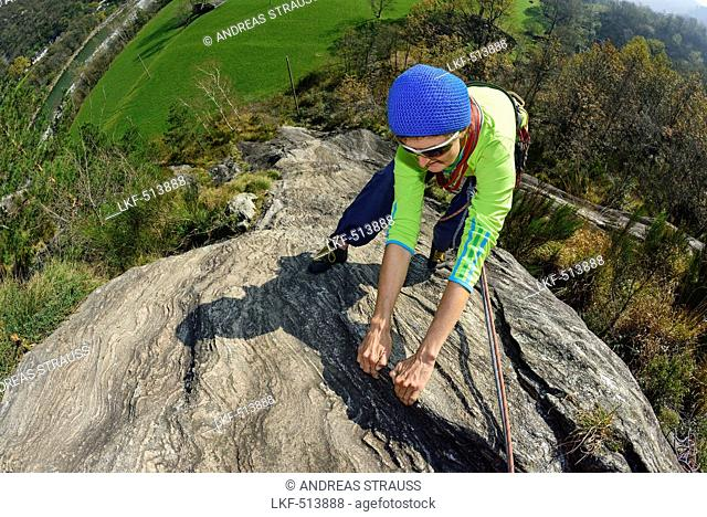Woman climbing on Gneiss rock, Torbeccio, valley of Maggia, Ticino, Switzerland