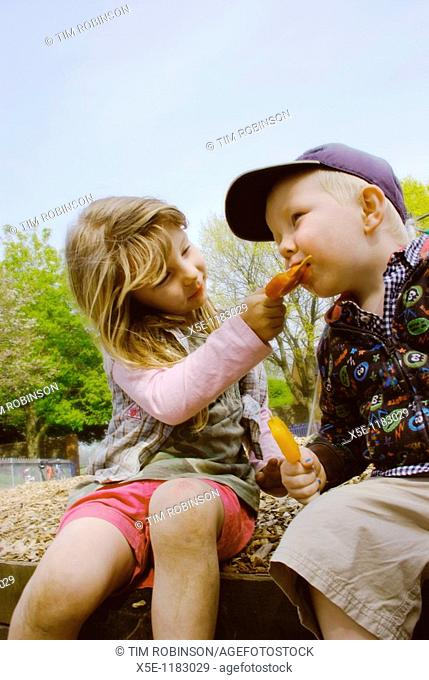 6 year girl sharing ice lolly with 3 year boy in playground