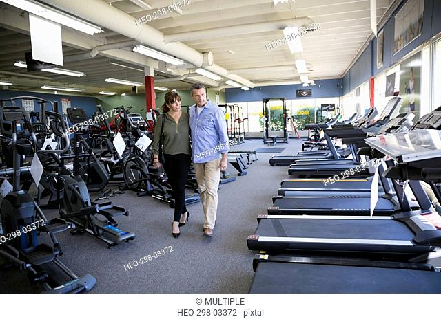 Couple browsing cardio machines in home gym equipment store