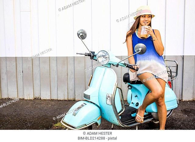 Pacific Islander woman drinking iced coffee on scooter