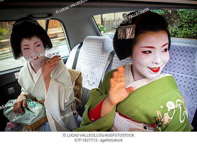 Fukuyu,geisha and Fukukimi,'maiko' geisha apprenticein taxi going to work They say goodbye at Oka san  Geisha's distric of Miyagawacho Kyoto  Kansai, Japan