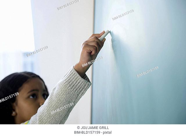 Mixed race student writing on chalkboard in classroom