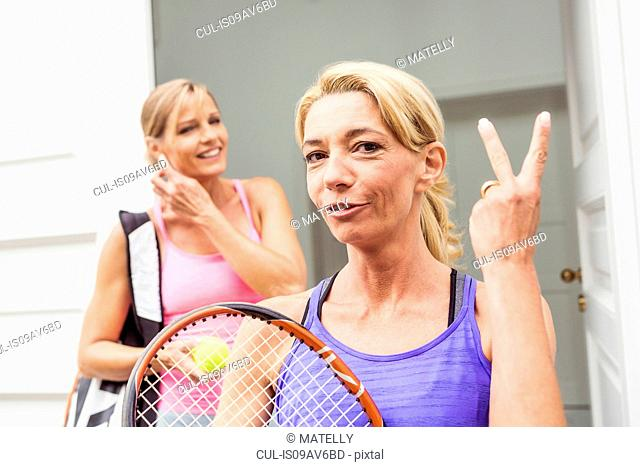 Portrait of two mature female tennis players, one making two finger gesture