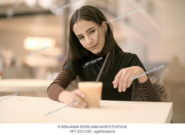 portrait of daydream woman holding coffee cup while enjoying break at table in café, in Munich, Germany