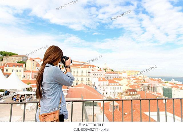 Young female tourist photographing in Alfama District, Lisbon, Portugal