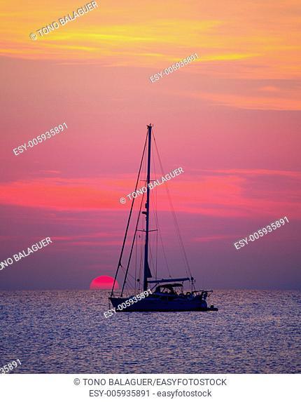 Ibiza sunset sun view from formentera Island with sailboat in Balearic Islands