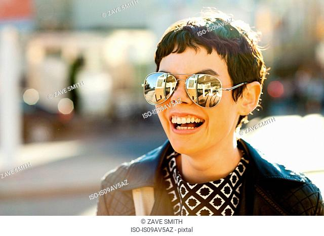 Portrait of mid adult woman, outdoors, wearing mirrored sunglasses