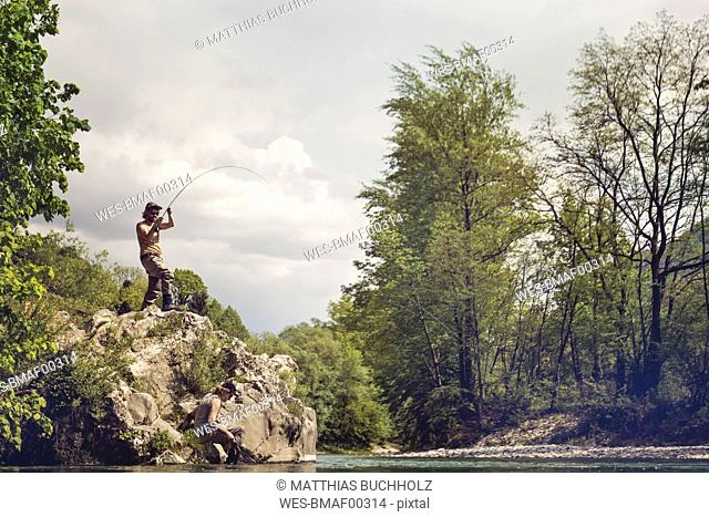 Slovenia, man fly fishing in Soca river standing on a rock