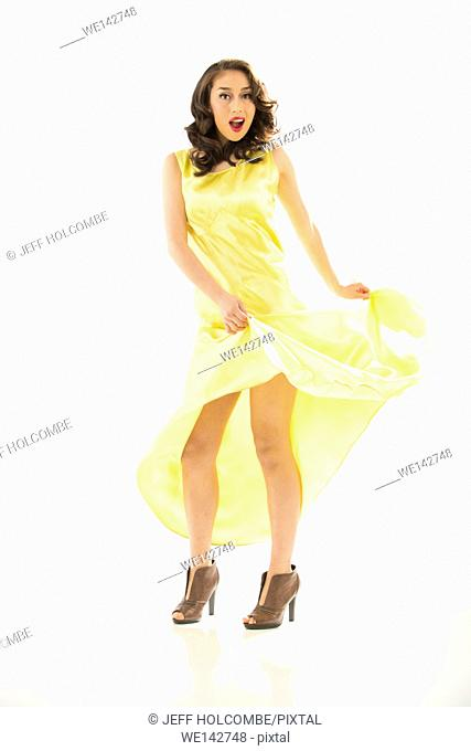 Beautiful young woman in vintage yellow dress, full length in brown heels, hands lifting dress