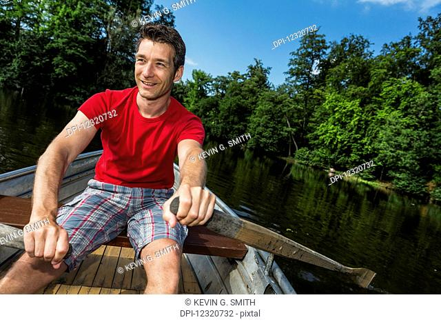 A smiling man wearing a red shirt rowing a boat down a calm river on a clear, sunny day; Darmstadt, Hessen, Germany