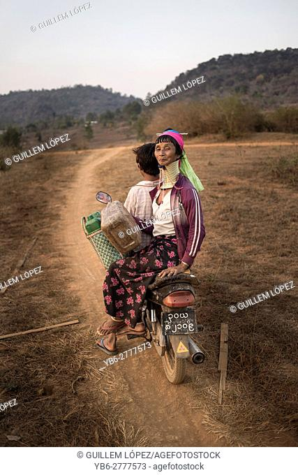 A Kayan woman riding on a motorbike in a dirt road, Kayah State, Myanmar