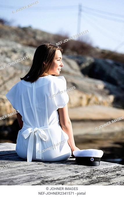 Woman in white dress sitting on jetty
