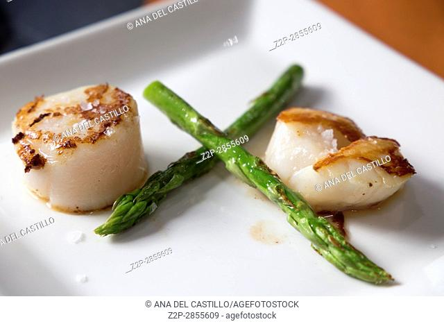 Roasted scallops with green asparagus on plate