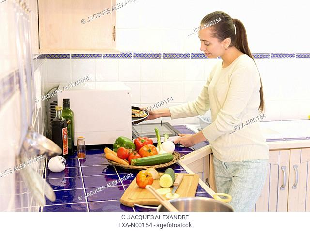 Woman in kitchen cooking