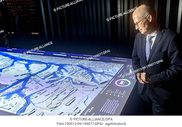 13 May 2019, Hamburg: Peter Tschentscher (SPD), Hamburg's first mayor, looks at a map of the harbour at the opening of the Discovery Docks