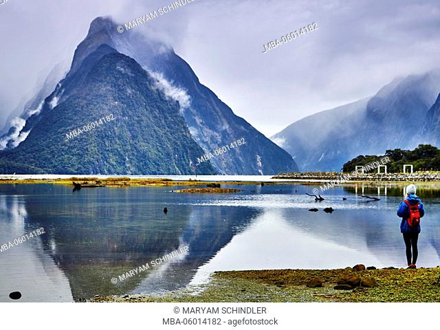 New Zealand, south island, Milford sound, tourist enjoys view, mountains disappear in clouds, mountain lakes, rainforest