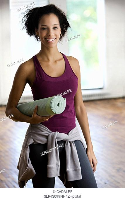 Young woman holding yoga mat, portrait