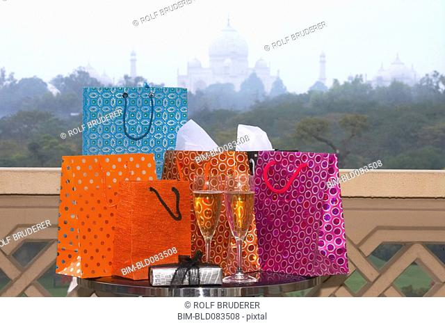 Group of luxurious shopping bags on table with Champagne