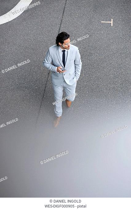 Walking businessman with smartphone crossing street