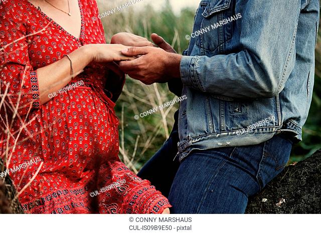 Mid section of romantic mid adult pregnant couple holding hands