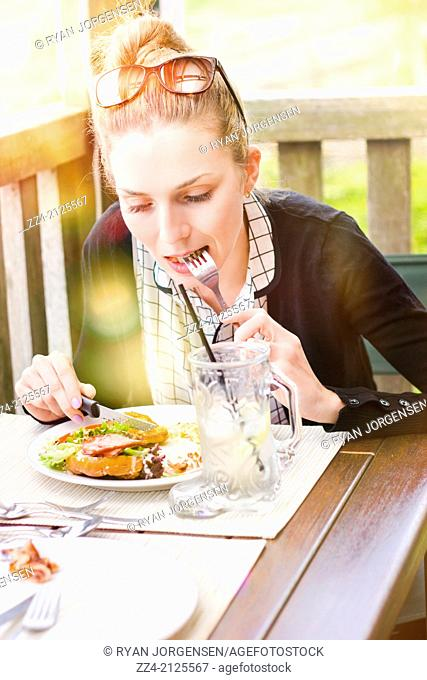 Sun flare image of an Australian person sitting on outdoor restaurant deck enjoying ham and salad sandwich with cutlery. Summer diner