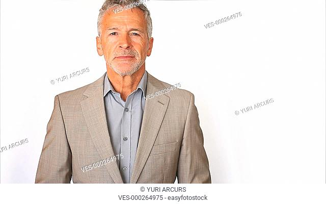 A handsome senior businessman in a suit looking composed isolated on white