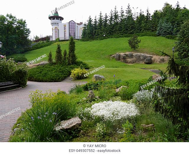 The palace with a beautiful green lawn around, with large stones, bushes, trees and a flower bed