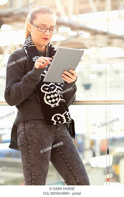 Young woman, using digital tablet, outdoors