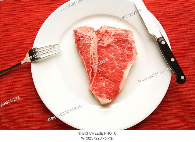 Raw steak on plate