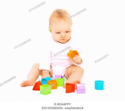 Little baby sitting and playing with colorful toys