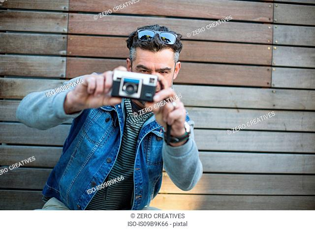 Portrait of mid adult man, taking photograph, using camera