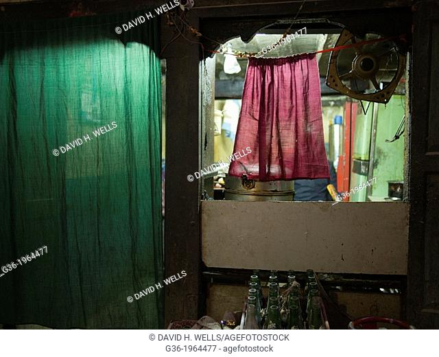 A small shop is obscured by a hanging piece of fabric in Patan, Nepal
